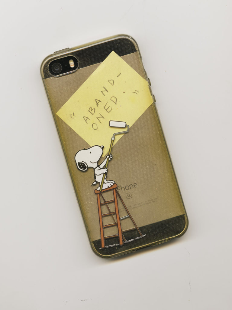flatbed scan of iphone with snoopy case and a postit